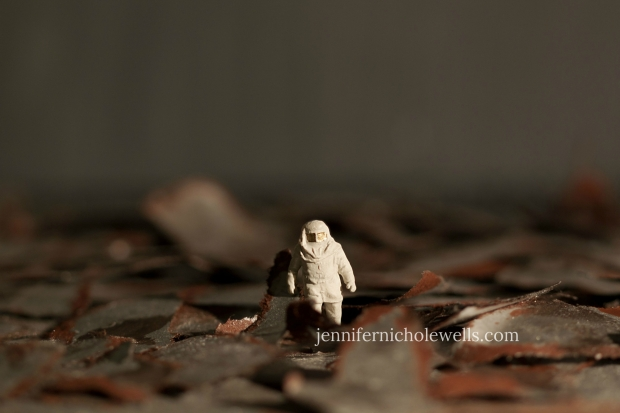 a miniature ho scale figure in field of rusty, torn apart metal (made from copy paper and paint)