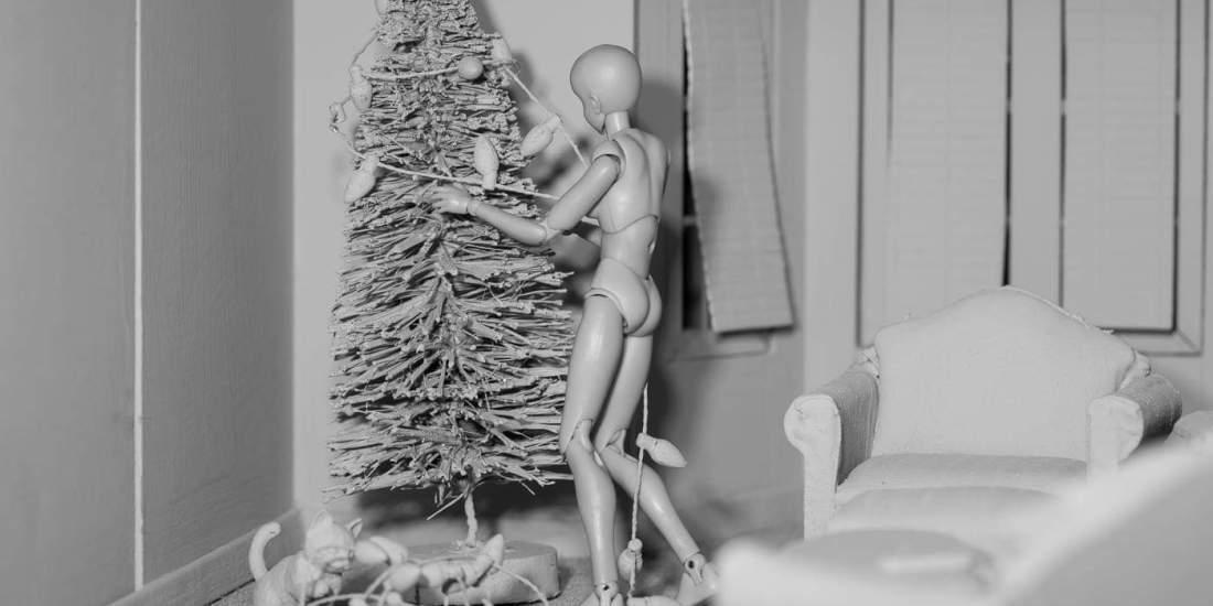 Figure putting lights on Christmas tree,