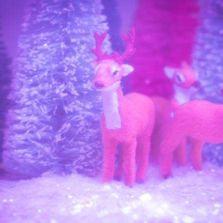 3 deer in pink forest clearing, toy photography by Tourmaline .
