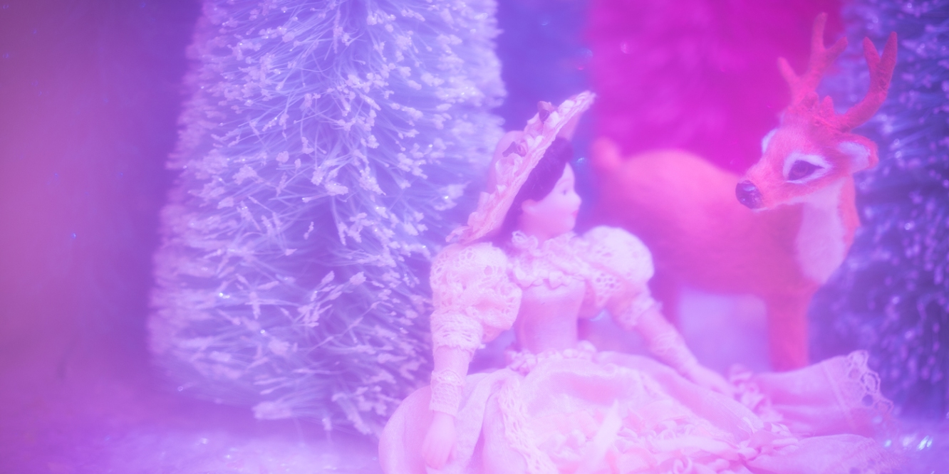 deer peering at Victorian woman in pink forest, toy photography by Tourmaline .