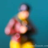 turquoise, deep red and yellow blurred portrait, toy photography by Tourmaline .