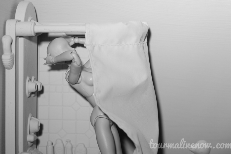 Figure showering in all grey environment, toy photograph by Tourmaline .