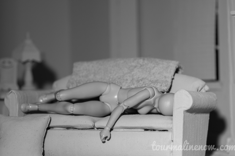 Figure sleeps on couch in all grey environment, toy photograph by Tourmaline .