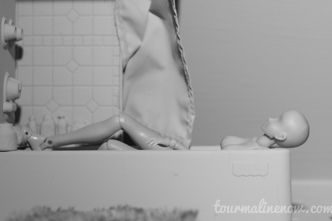 Figure taking bath in all grey environment, toy photograph by Tourmaline .