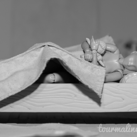 Figure lays in bed holding doll in all grey environment, toy photograph by Tourmaline .