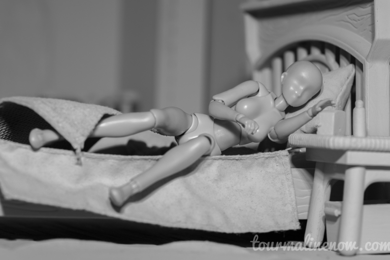 Figure turns off alarm in all grey environment, toy photograph by Tourmaline .