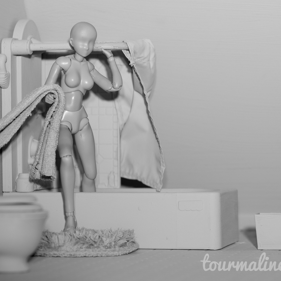 Figure steps out of shower in all grey environment, toy photograph by Tourmaline .