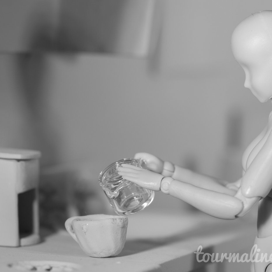 Figure pours coffee in all grey environment, toy photograph by Tourmaline .