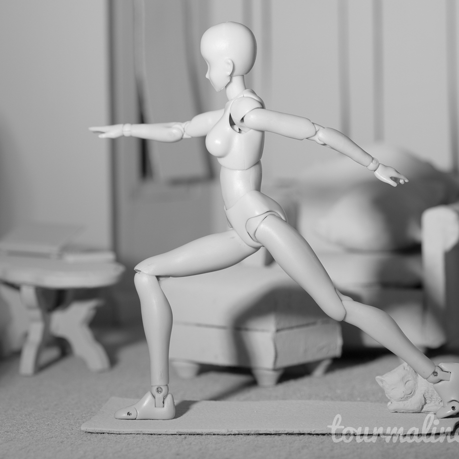 Figure does yoga in all grey environment, toy photography by Tourmaline .