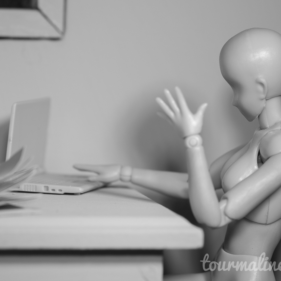 Figure looks frustrated at laptop in all grey environment, toy photography by Tourmaline .