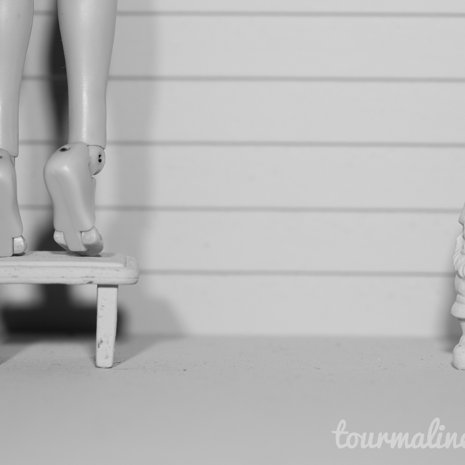 Figure stands on tip toes on step stool in all grey environment, toy photography by Tourmaline .