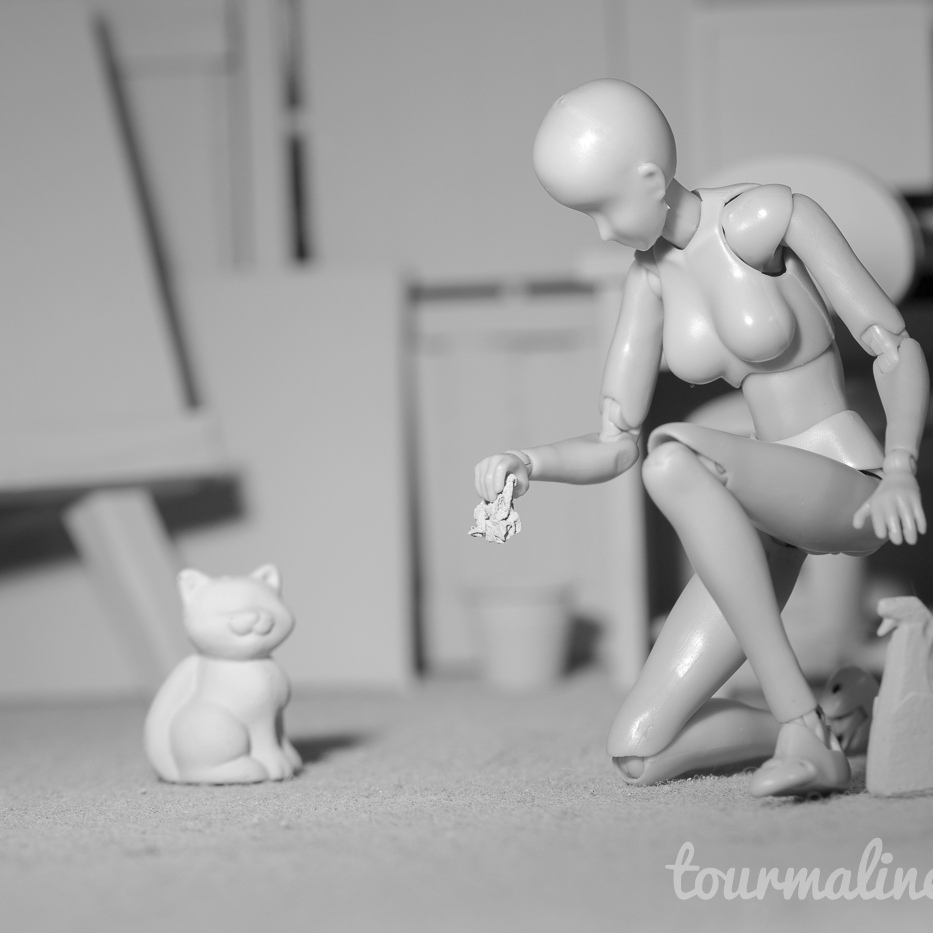 Figure cleans hairball in all grey environment, toy photography by Tourmaline .