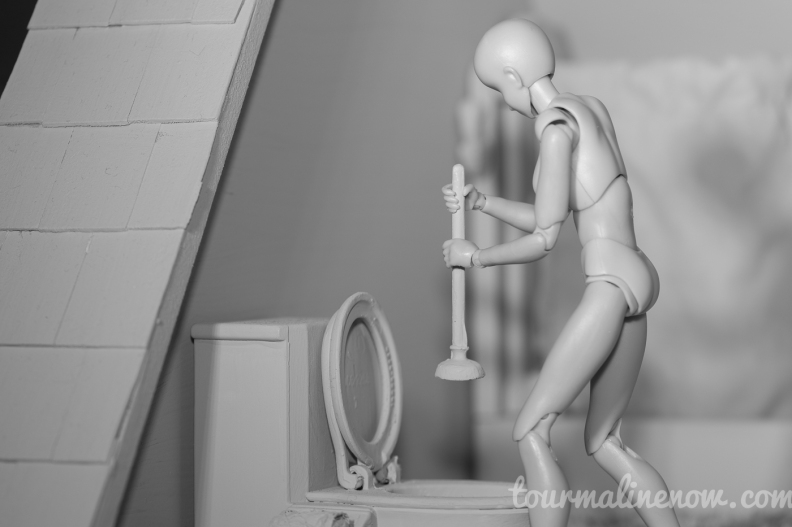 Figure plunges toilet in all grey environment, toy photography by Tourmaline .