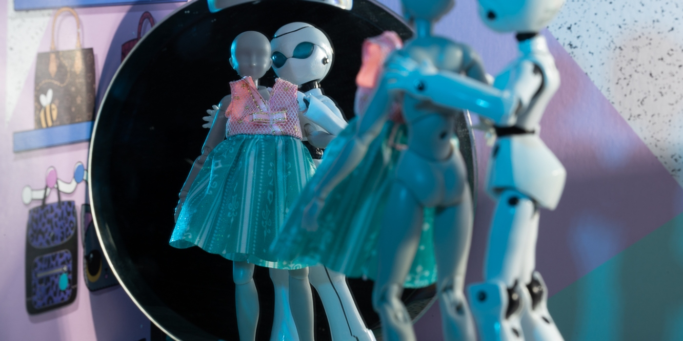 Figure stands at mirror, robot hold up dress, toy photography by Tourmaline .