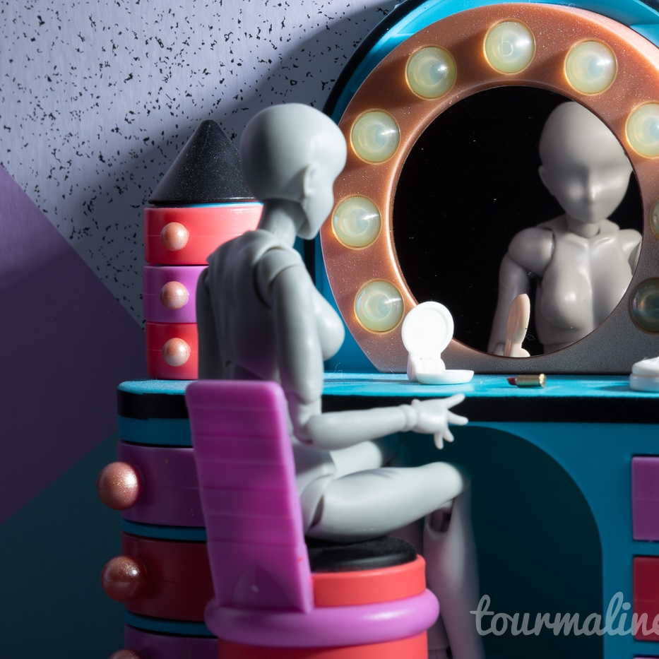 FIgure sitting at vanity, toy photography by Tourmaline .