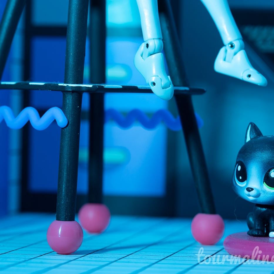 Figures feet dangle from chair, cat on floor, toy photography by Tourmaline .