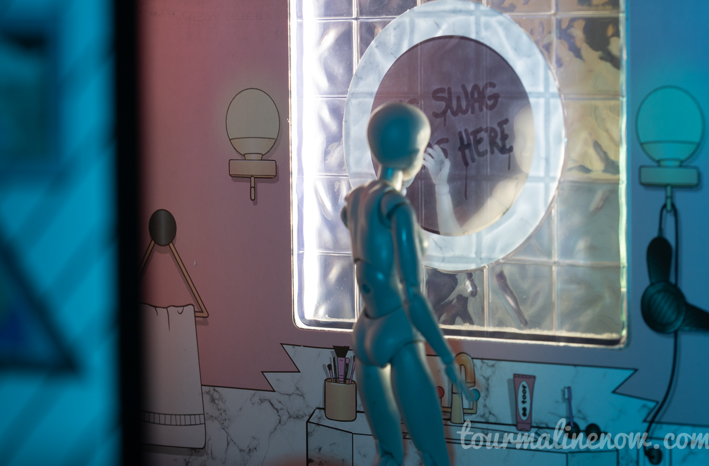 Figure touches bathroom mirror with writing on it, toy photography by Tourmaline .