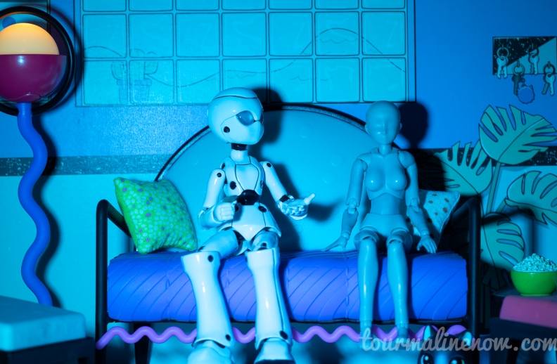 Robot explaining something to a fear stricken figure sitting on a couch, toy photography by Tourmaline .