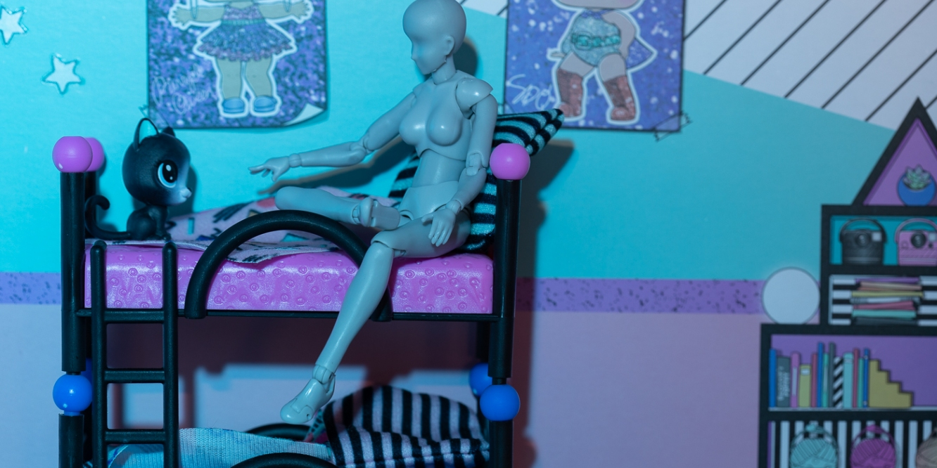 Figure sits on top bunk of bed reaching out to cat, toy photography by Tourmaline .