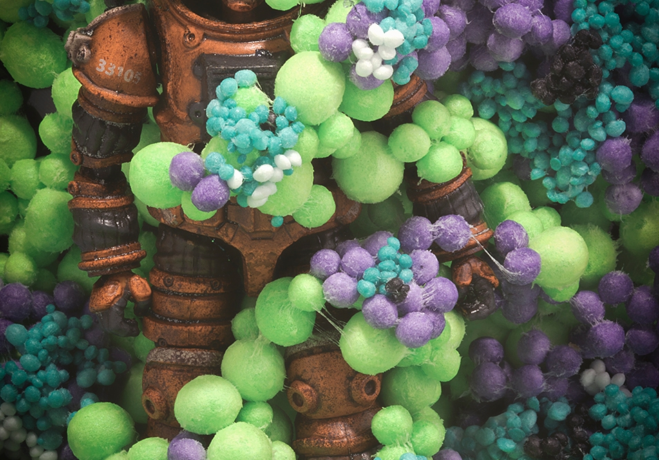 Astronaut covered in putple, white, aqua and lime green growth, toy photography by Tourmaline .