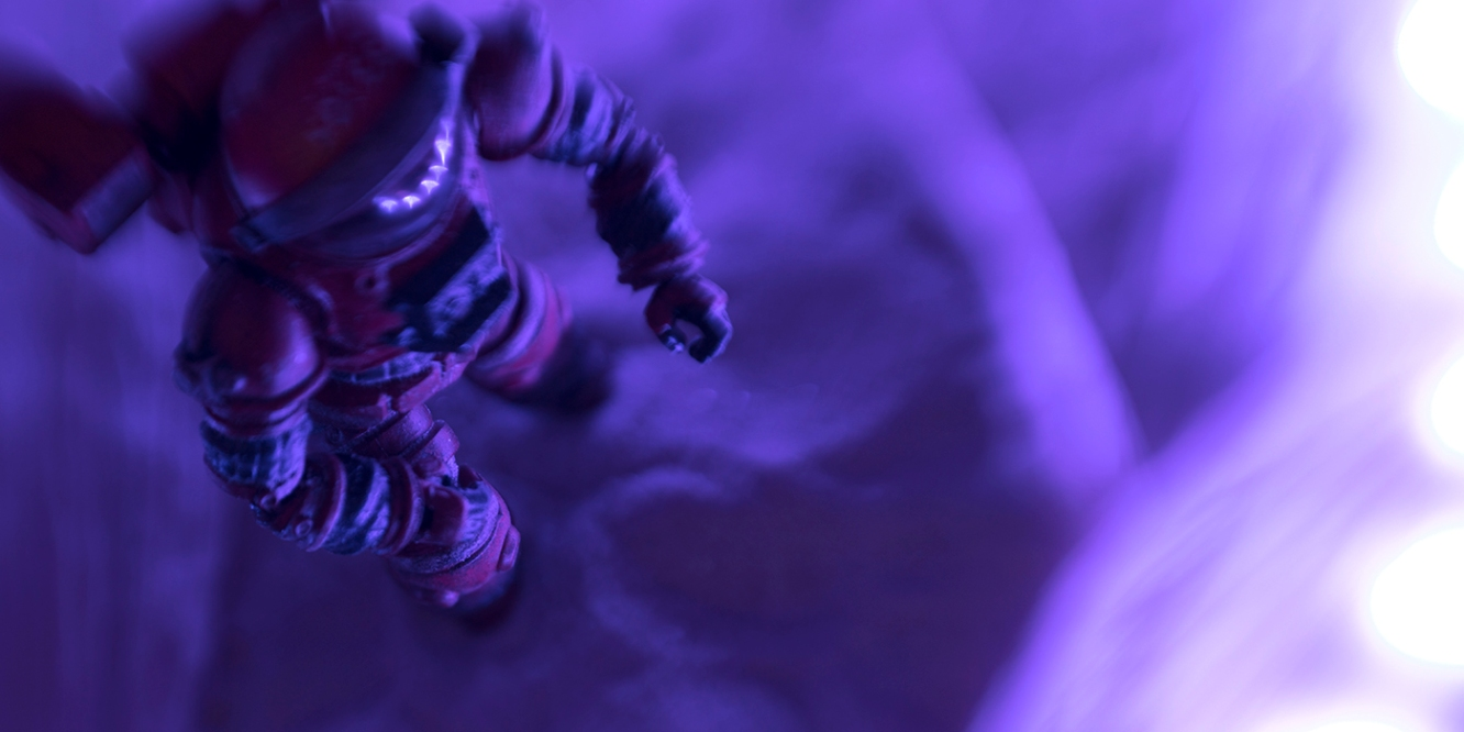Astronaut seen from above in purple tinted scene, toy photography by Tourmaline .