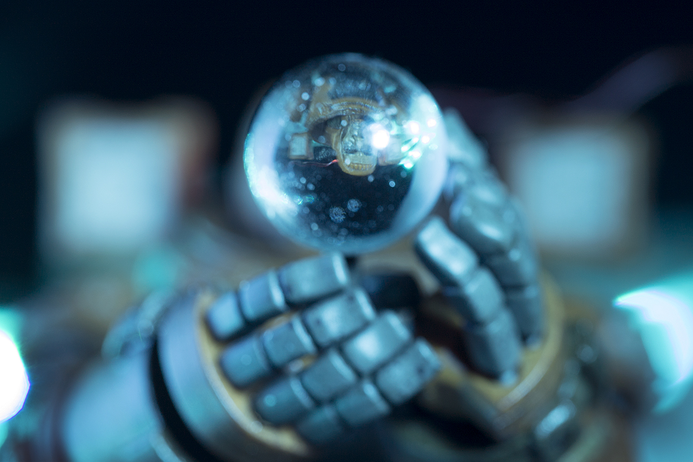 Astronaut mech sut hands holding glass orb with face reflected, toy photography by Tourmaline .