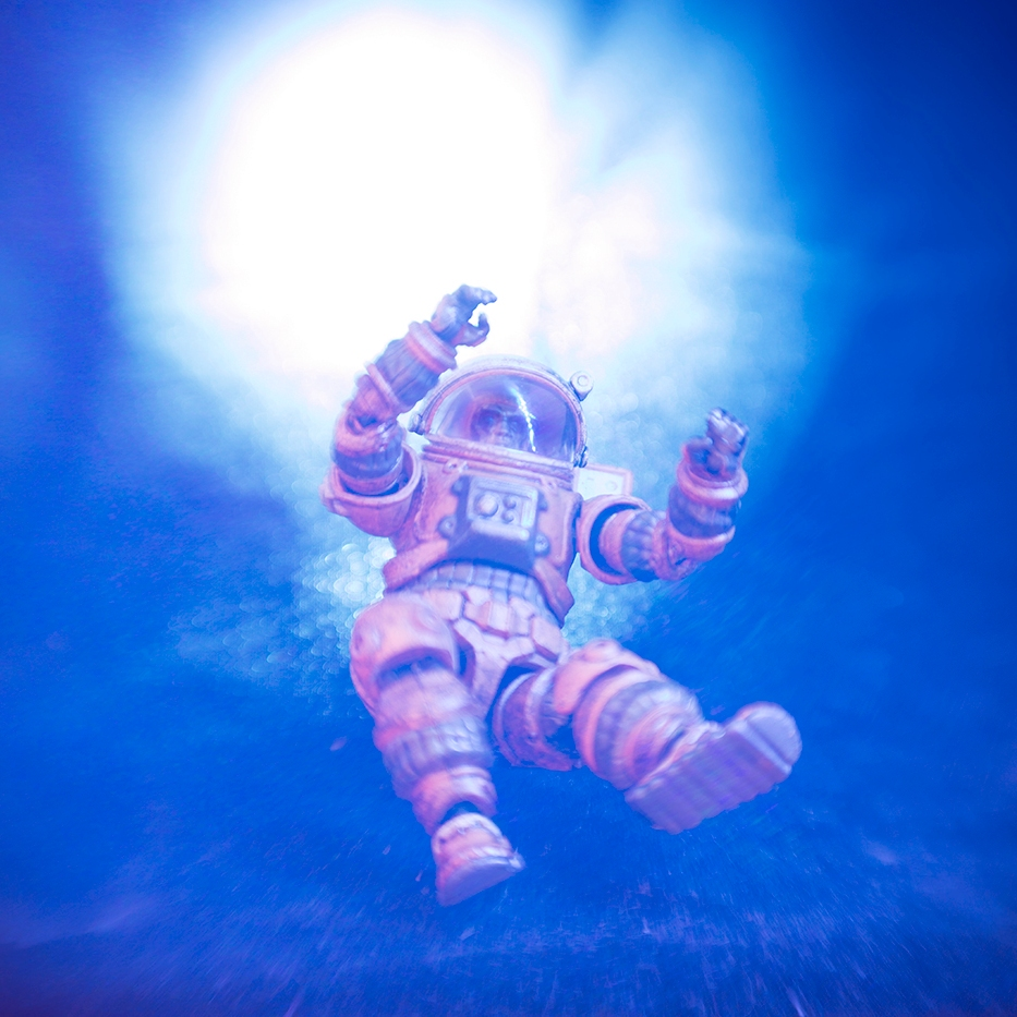 Astronaut being sucked into a vortex, toy photography by Tourmaline .