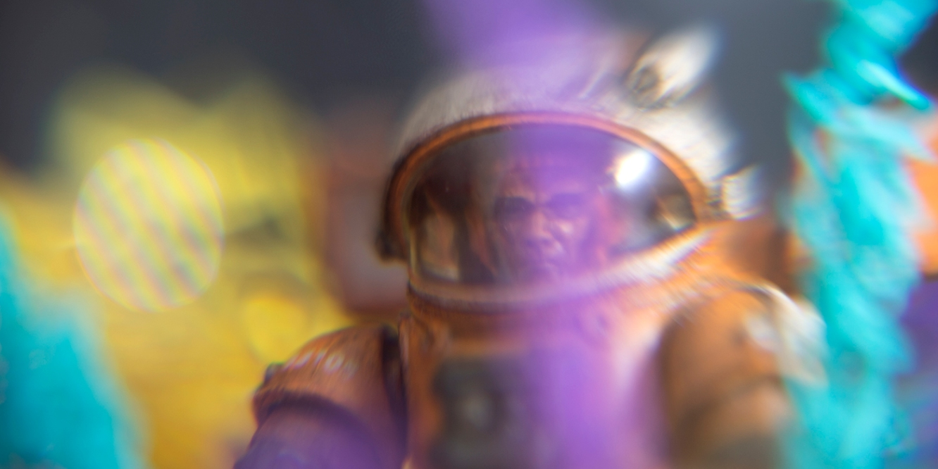 Astronaut surrounded by purple, aqua and yellow stripes of color, toy photography by Tourmaline .